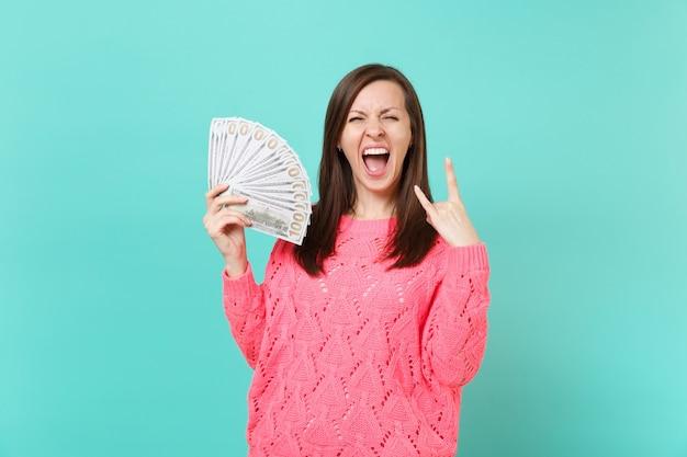 Donna pazza in maglione rosa che urla, tiene in mano un sacco di banconote in dollari, denaro contante, raffigurante un segno di corna rock heavy metal isolato su sfondo blu. concetto di stile di vita della gente. mock up copia spazio.