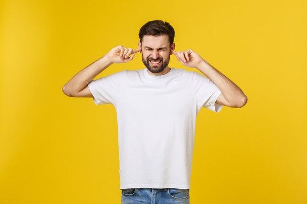 Giovane uomo barbuto pazzo nella posa blu della camicia isolato sull'arancia gialla nello studio concetto di stile di vita della gente derisione sullo spazio della copia