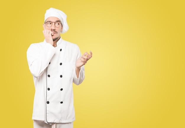 Pazzo giovane chef che fa un gesto nervoso