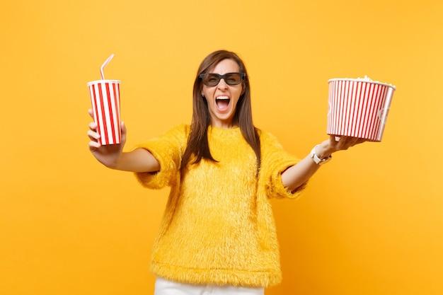 Giovane donna pazza in occhiali 3d imax che urla, guarda film, tiene in mano un secchio di popcorn, una tazza di plastica di cola o soda isolata su sfondo giallo. persone sincere emozioni nel cinema, nello stile di vita.