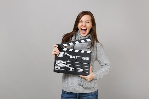 Giovane donna pazza in maglione grigio, sciarpa urlante, con in mano un classico film nero che fa ciak isolato su sfondo grigio. stile di vita sano, persone sincere emozioni, concetto di stagione fredda.