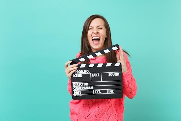 Giovane donna pazza in maglione rosa lavorato a maglia che urla tenere in mano classico film nero che fa ciak isolato su sfondo blu muro, ritratto in studio. concetto di stile di vita della gente. mock up copia spazio.