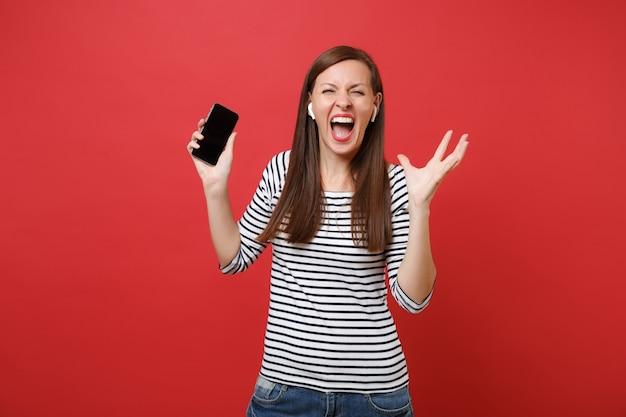Giovane donna pazza con gli auricolari wireless che urla, tiene il telefono cellulare con musica d'ascolto dello schermo vuoto nero vuoto isolato su sfondo rosso. persone sincere emozioni, stile di vita. mock up copia spazio.