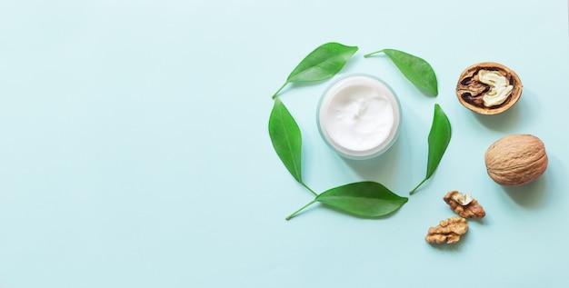 Bottiglia di crema con foglie fresche di foglie verdi e noci. cosmetici naturali di concetto. trattamento di aromaterapia. vista dall'alto e copia spazio disteso.