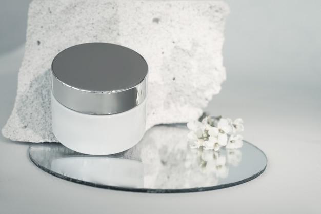 Scatola crema su pezzo di cemento. la struttura porosa del calcestruzzo è associata alla trama della pelle umana.