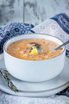 Zuppa di crema di formaggio con funghi, patate e pollo, delizioso primo piatto in tavola con tovaglia blu, verticale