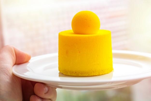 Cheesecake alla crema con mango e frutto della passione su un piatto in mano a una persona. minicort su un piatto