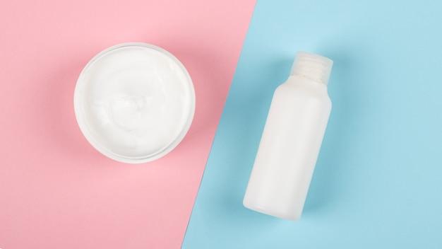 Cosmetici crema su sfondo rosa blucura della pelle di bellezza