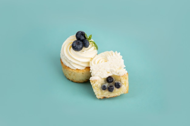 Cupcakes alla crema con mirtilli su sfondo blu