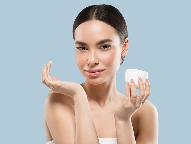 Crema viso donna cosmetici cura della pelle sana bellezza ritratto isolato su bianco colore di sfondo blue