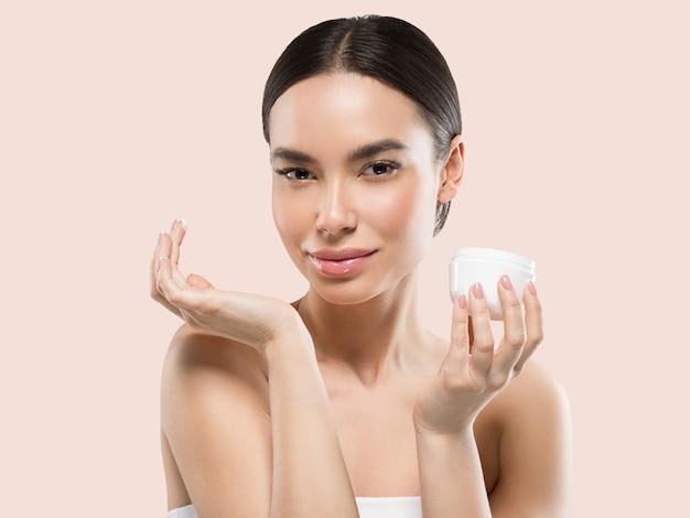 Crema viso donna cosmetici cura della pelle sana bellezza ritratto isolato su bianco colore di sfondo rosa