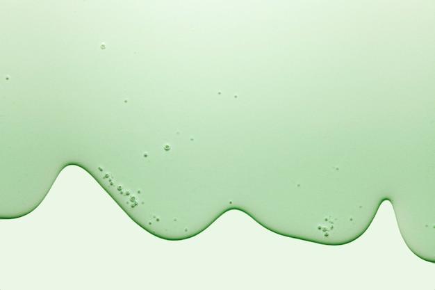 Struttura del campione cosmetico trasparente gel crema verde con bolle isolate su priorità bassa verde