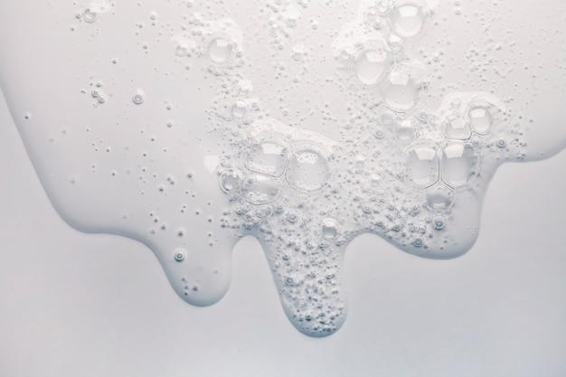 Gel crema trasparente campione cosmetico texture con bolle su sfondo grigio