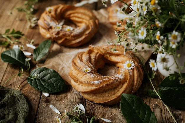 Il soffio crema suona su un fondo di legno fra i fiori dei camomiles.
