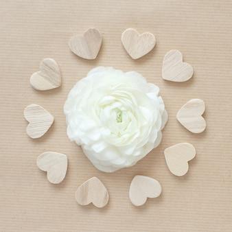 Fiore di ranuncolo crema in un cerchio di cuori su vista dall'alto di carta beige