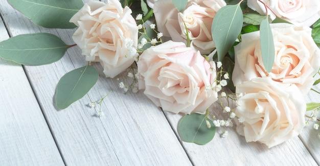 Rose crema ed eucalipto. disposizione dei fiori delicata su un fondo di legno bianco.