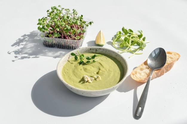 Zuppa di crema con formaggio blu, pane e microgreens su sfondo bianco. cibo pulito, dieta, concetto di cibo detox.