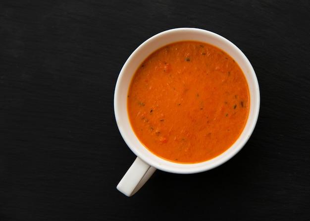 Zuppa di crema con peperoni arrostiti e pomodori sulla banda nera, vista dall'alto