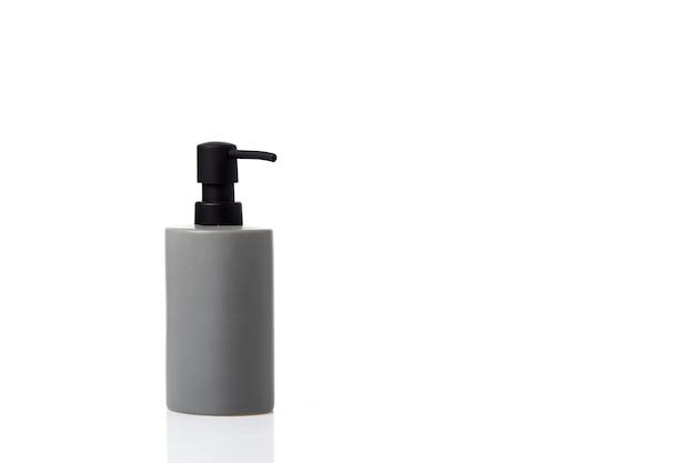Vaso per bottiglia crema spa pompa per sapone antisettico su superficie bianca