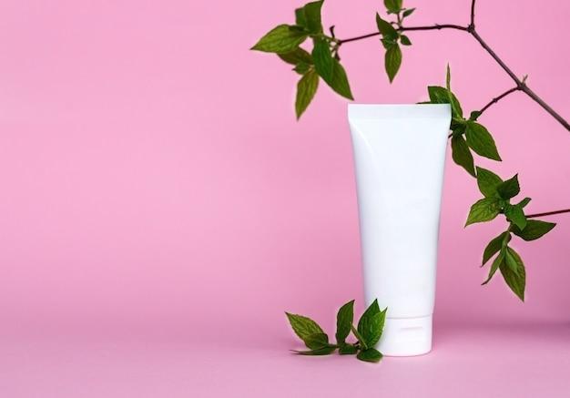 Tubo crema su sfondo rosa prodotto cosmetico per la cura della pelle vuoto confezione in plastica bianca lozione senza marchio balsamo crema mani dentifricio mockup