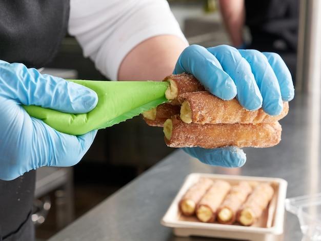 Cannoli ripieni di crema preparati da uno chef, non vengono mostrati volti