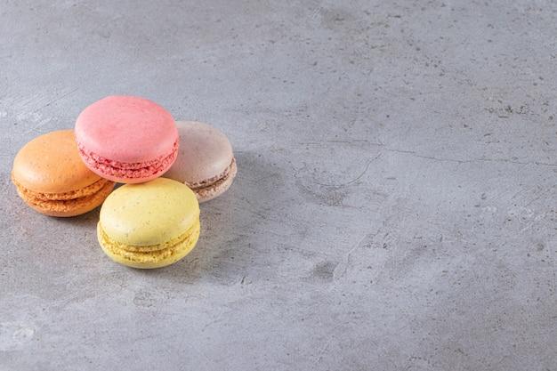 Amaretti dolci colorati cremosi posti sulla tavola di marmo.