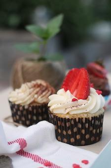 Cupcake cremosi decorati con cuore di fragola e zucchero
