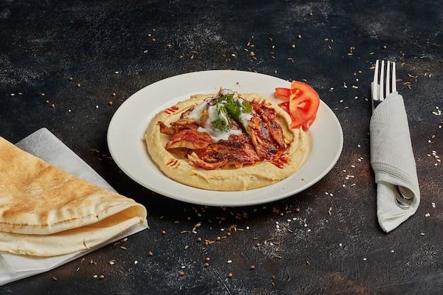 Hummus cremoso con carne macinata di montone piccante su sfondo scuro