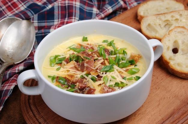 Zuppa cremosa di patate al forno con pancetta e formaggio, cipolle verdi