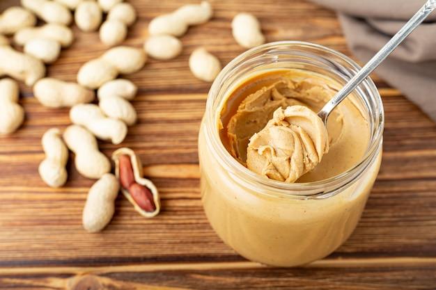 Crema di arachidi cremosa in barattolo di vetro aperto, burro di arachidi in cucchiaio. arachidi nella buccia sparsi sul tavolo di legno marrone.