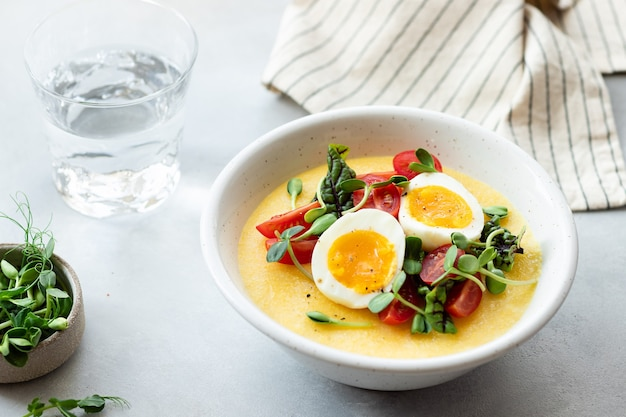 Polenta cremosa con uova verdure fresche microgreens su tavola grigia cucina italiana