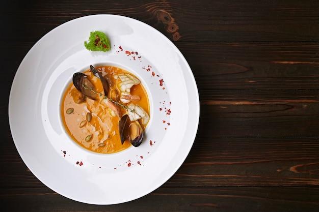 Zuppa cremosa di zucca con frutti di mare, cozze, gamberi, calamari, in un piatto bianco, su una superficie di legno