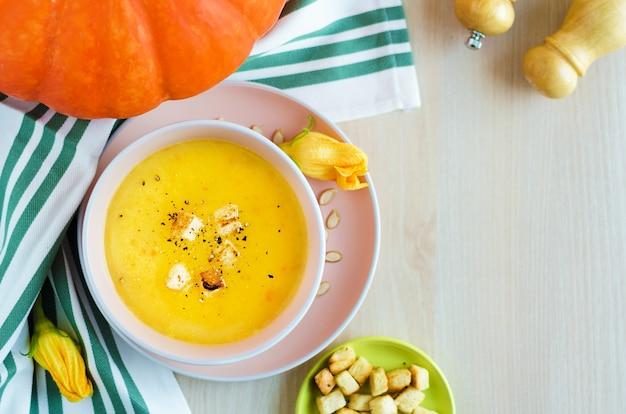 Zuppa cremosa di zucca con semi e crostini di pane in una ciotola.