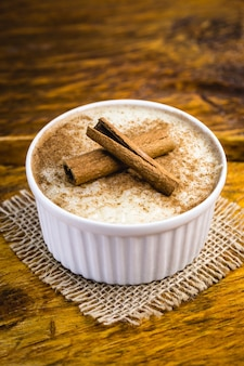 Budino di riso cremoso cosparso di cannella, tipico dolce brasiliano.