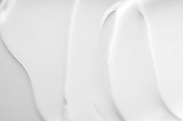 Primo piano del prodotto di mousse di lozione per la cura della pelle cremosa. crema bianca, texture shampoo, crema solare sfondo striscio cosmetico. swatch crema di bellezza idratante.