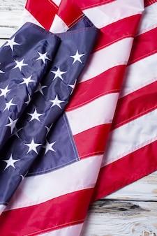 Bandiera piegata dell'america. bandiera su fondo di legno bianco. strisce luminose e stelle. banner di persone orgogliose.