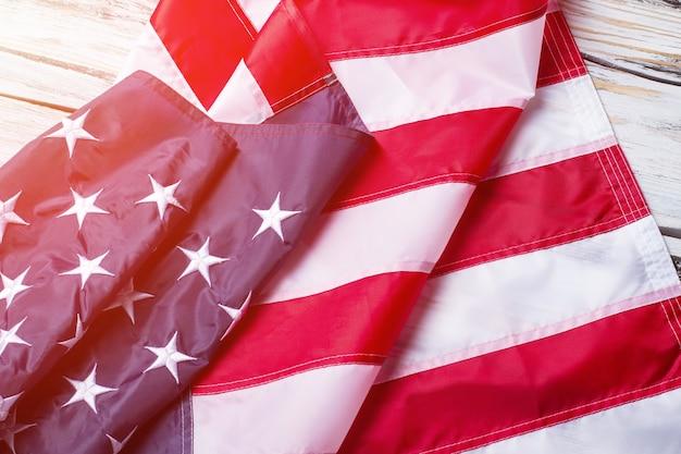 Bandiera piegata degli stati uniti. bandiera nazionale usa alla luce del sole. banner posa su mensola in legno. pace, prosperità e futuro.