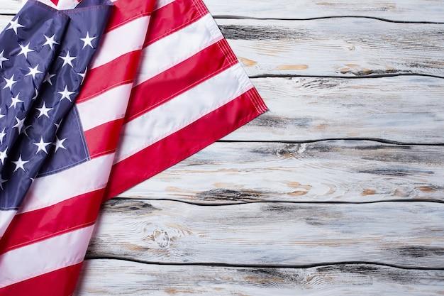 Bandiera usa piegata. bandiera nazionale su fondo in legno. libertà e solidarietà. paese guidato dalla democrazia.