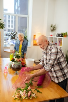Creazione di bouquet. piacevole uomo invecchiato che avvolge un fiore mentre crea un bouquet