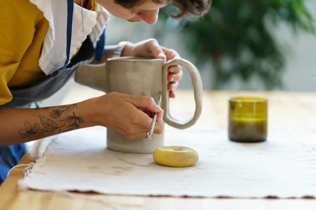 Creazione di stoviglie in ceramica in laboratorio di ceramica studio concentrato artista ragazza lavora su brocca fatta a mano