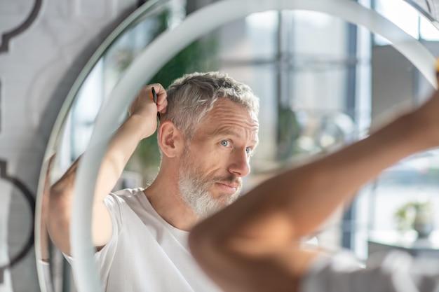 Creare un'acconciatura. un uomo che si pettina i capelli al mattino