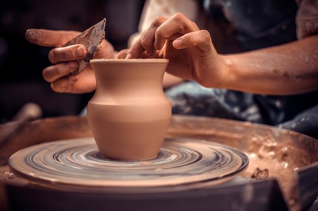 Creare un barattolo o un vaso. maestro coccio. fare brocca di argilla. lo scultore nel laboratorio fa una brocca con un primo piano di terracotta.