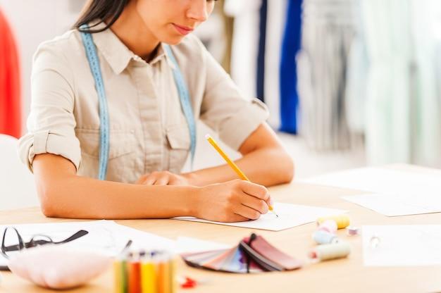 Creazione di capolavori. primo piano di una giovane donna che disegna mentre è seduta al suo posto di lavoro