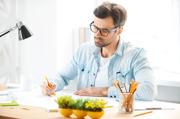 Creazione di un nuovo progetto. bel giovane in camicia e occhiali che lavora al suo progetto mentre è seduto al suo posto di lavoro