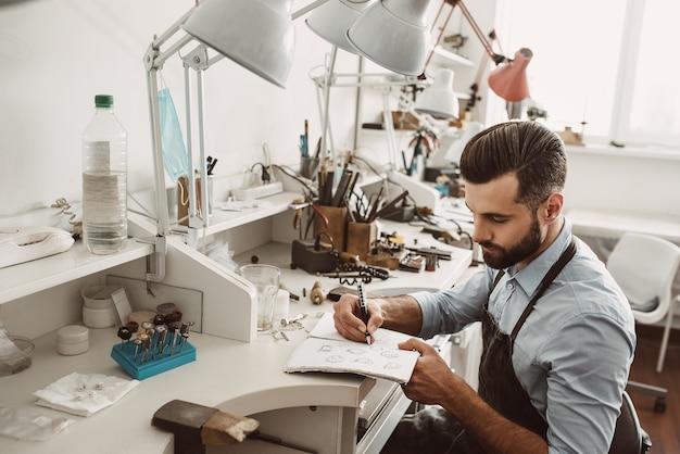 Creazione di schizzi. ritratto di giovane gioielliere barbuto che disegna uno schizzo di un nuovo progetto mentre è seduto nel suo laboratorio