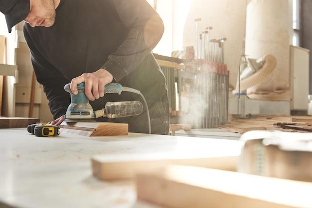 Creazione di falegnameria unica e personalizzata, l'operaio macina il legno della rettificatrice angolare a sua volta
