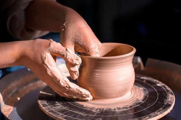 Creazione di vaso di primo piano di argilla. maestro coccio. lo scultore nel laboratorio fa una brocca con un primo piano di terracotta.