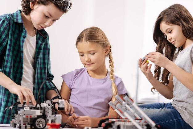 Creazione del progetto nei dettagli. bambini attenti amichevoli positivi che si siedono nel laboratorio di robotica e riparano i dispositivi informatici mentre hanno lezione di scienze