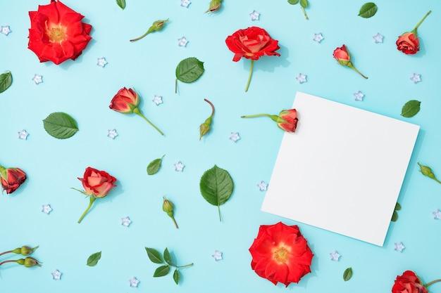 Disposizione creativa di fiori e foglie rossi su blu pastello con nota di carta di carta.