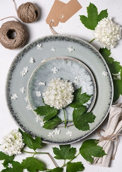 Composizione creativa con fiori bianchi che sbocciano palle di neve e piatti verdi